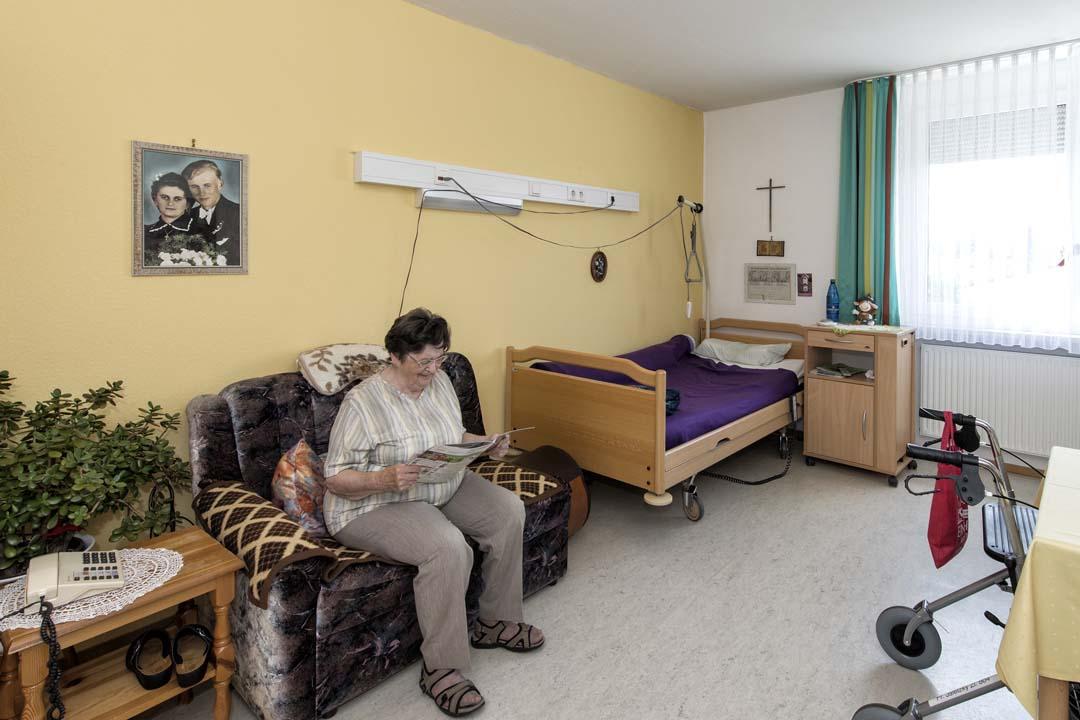 Dieses Bild zeigt eine Seniorin lesend in ihrem Zimmer, das mit einer gemütlichen Couch, einem Bett, einem Tisch und weiteren Einrichtungsgegenständen ausgestattet ist.