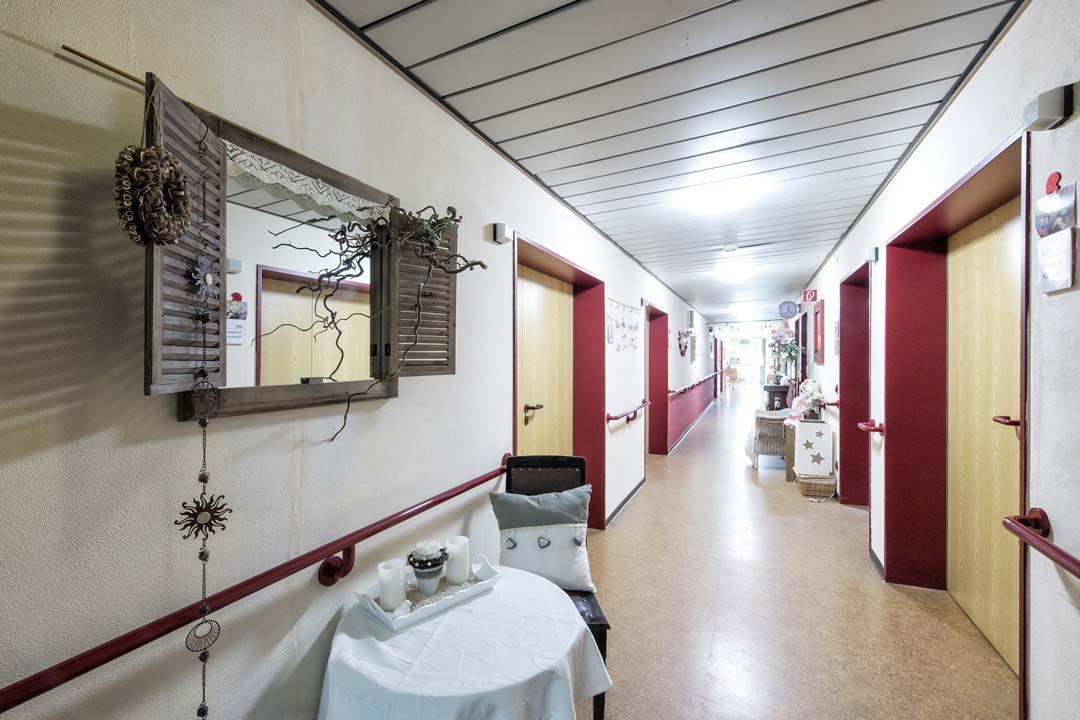Dieses Bild zeigt einen Flur im AWO Seniorenzentrum Weißenburg: ein farbiger Handlauf, ein Tisch und Dekorationen