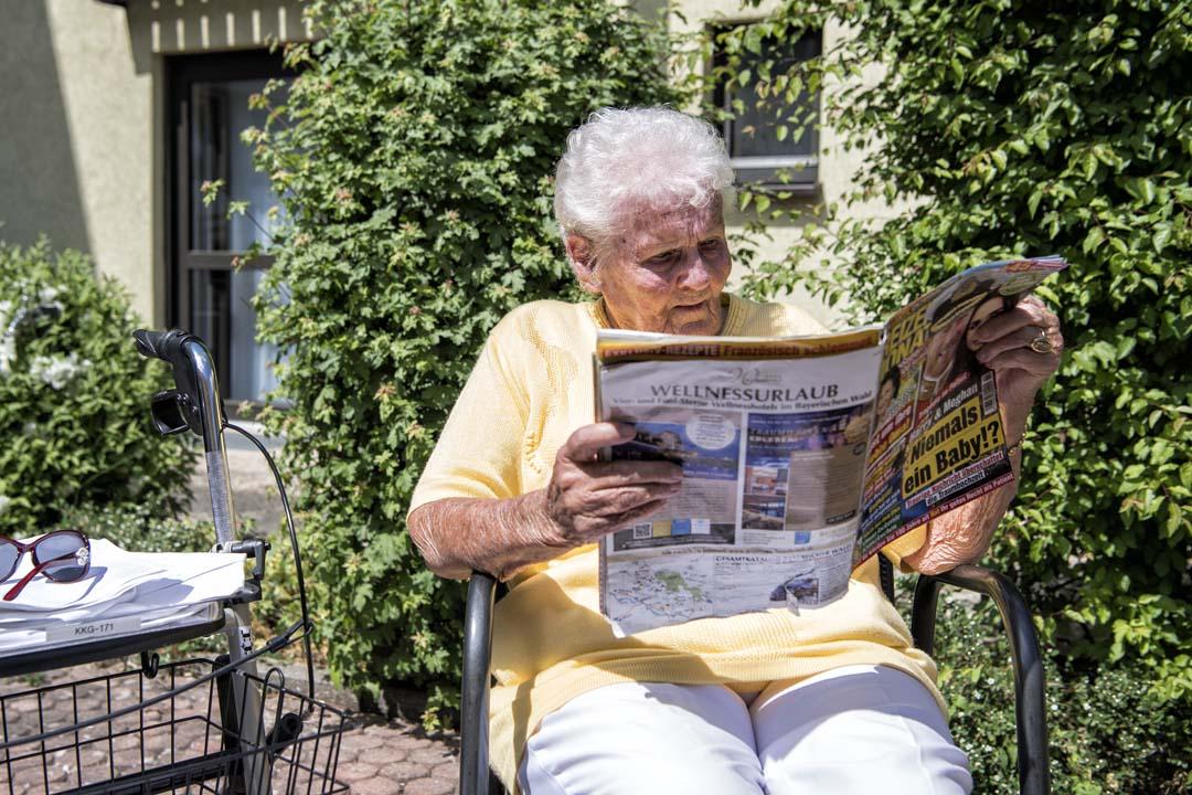 Dieses Bild zeigt eine Seniorin, die im Garten des AWO Seniorenzentrums Weißenburg in der Sonne sitzt und liest