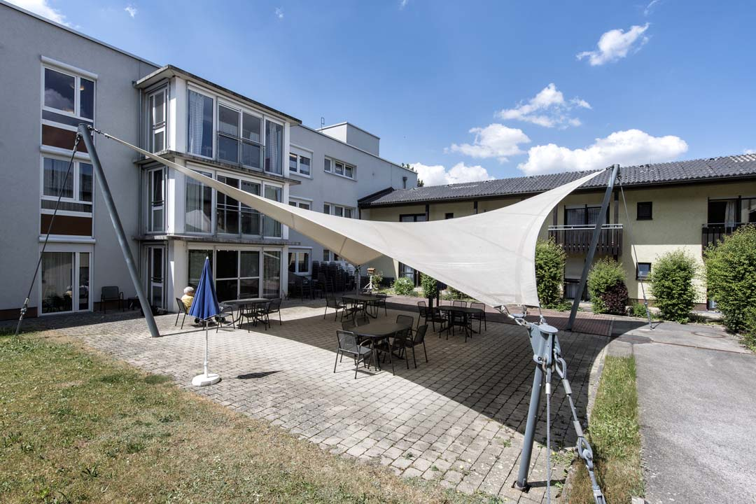 Dieses Bild zeigt das AWO Seniorenzentrum Weißenburg von außen: Sitzgelegenheiten mit Sonnensegel