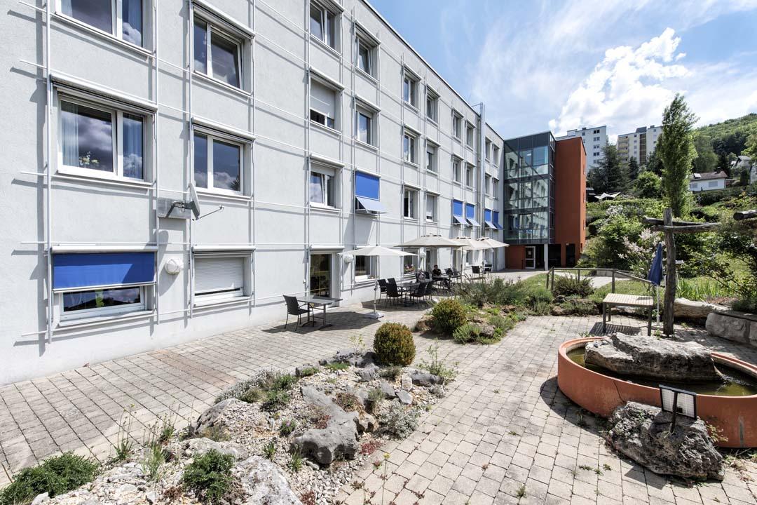 Dieses Bild zeigt das AWO Seniorenzentrum Weißenburg von außen: ein Garten mit einem schönen Freisitz und einem kleinen Teich