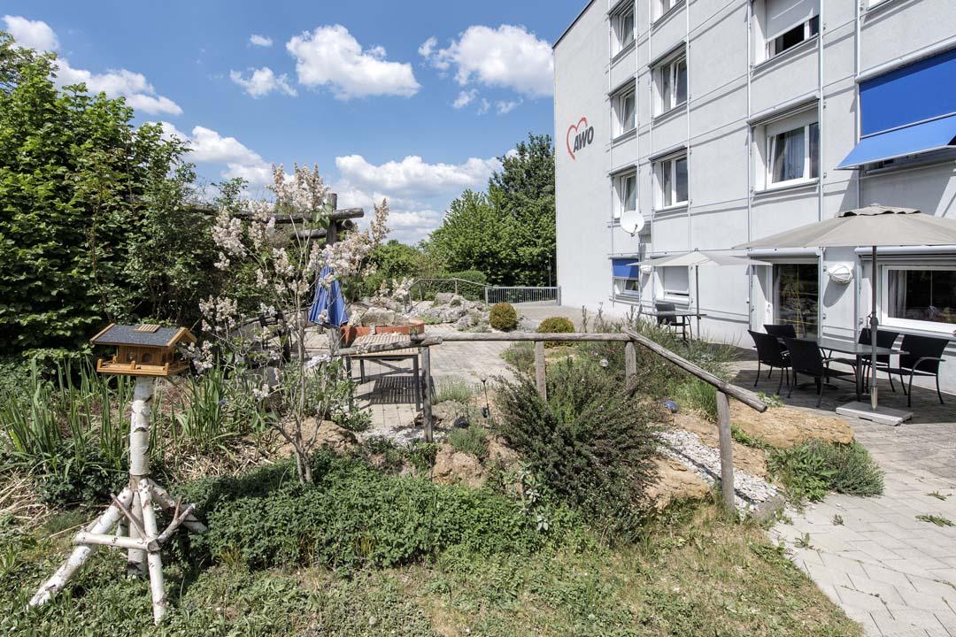 Dieses Bild zeigt das AWO Seniorenzentrum Weißenburg von außen: ein Garten mit einem schönen Freisitz