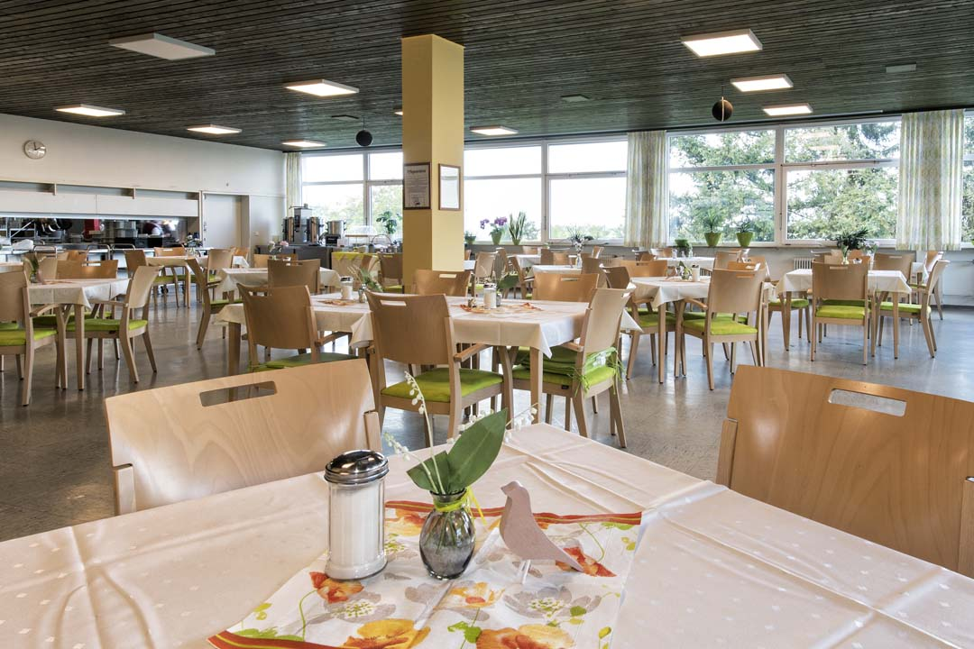 Dieses Bild zeigt den Speisesaal im AWO Seniorenzentrum Weißenburg: schön gedeckte Tische und viele Fenster
