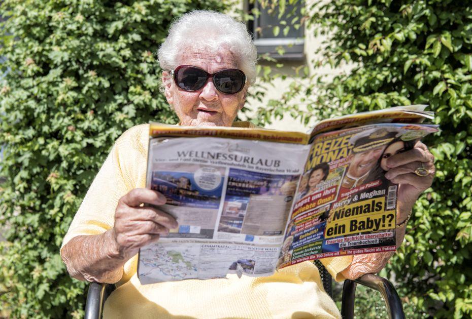 Dieses Bild zeigt eine Seniorin die gemütlich in der Sonne sitzt und eine Zeitschrift liest