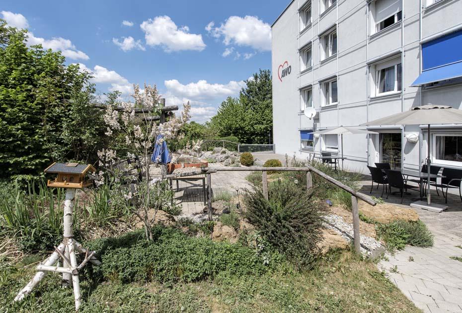 Dieses Bold zeigt einen der Gärten des AWO Sozialzentrums Weißenburg mit einem Vogelhäuschen und einladenden Sitzgelegenheiten