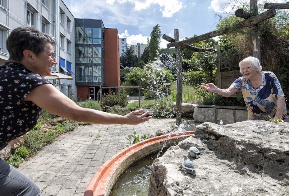 Dieses Foto zeigt zwei Damen, die sich an einem Brunnen mit Wasser bespritzen und Spaß haben