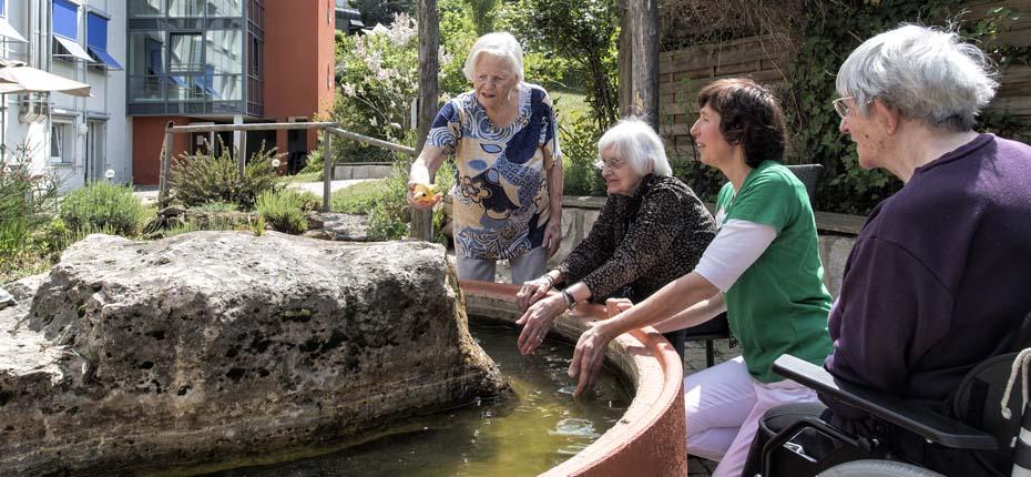 Dieses Bild zeigt Seniorinnen und eine Betreuerin am Brunnen, alle lachen und haben Spaß