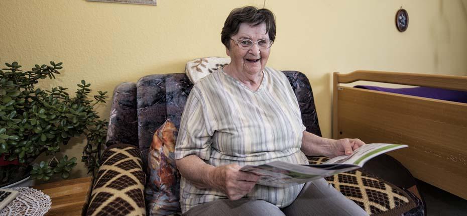 Dieses Foto zeit eine alte Dame, die in ihrem Zimmer sitzt und liest