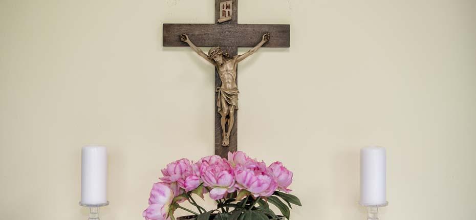 Dieses Bild zeigt ein Kreuz, zwei Kerzen und Blumen