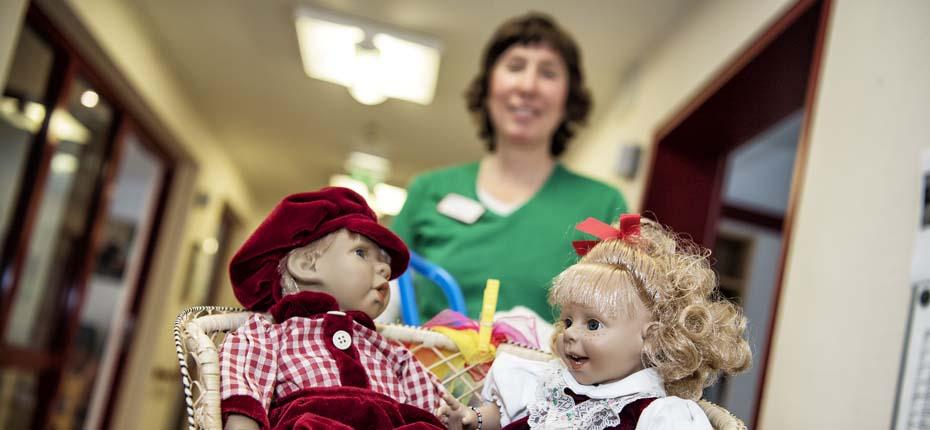 Dieses Foto zeigt eine Pflegerin die zwei Puppen auf einem Wagen schiebt