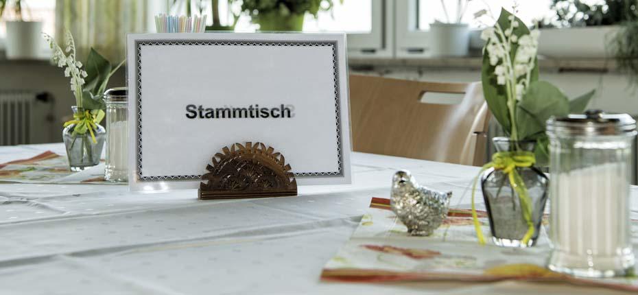 Dieses Foto zeigt ein Stammtisch-Schild auf einem schön gedeckten Tisch