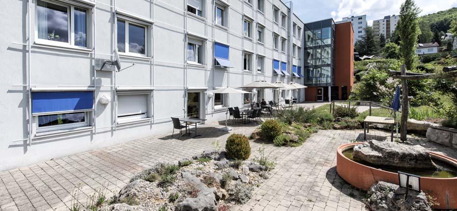 Dieses Bild zeigt das Gebäude mit dem Garten des AWO Sozialzentrums Weißenburg und einer Außenterrasse mit Sonnenschirmen und Stühlen