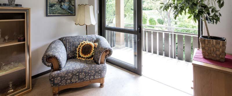 Dieses Foto zeigt eine gemütliche Couch vor einem großen Balkon