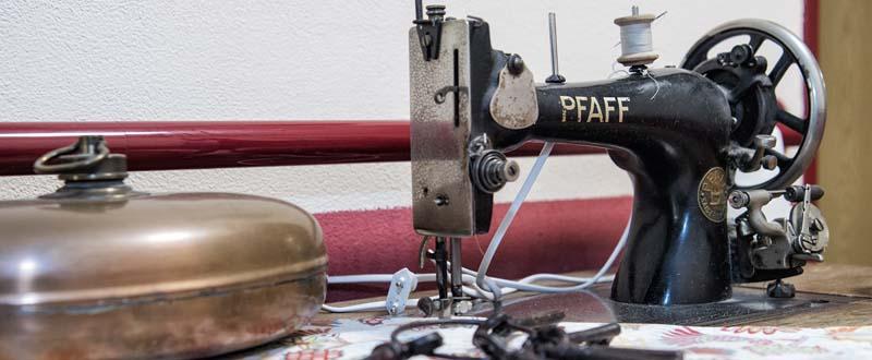 Dieses Foto zeigt eine alte Nähmaschine und eine Bettpfanne